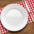 Empty plate with fork and knife on tablecloth over wooden — Stock Photo #57132813