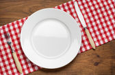 Empty plate with fork and knife on tablecloth over wooden — Stock Photo