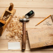 Carpenter tools, plane, hammer,meter, nails,shavings, and chisel over wood table — Stok fotoğraf #57440717