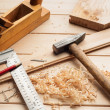 Carpenter tools, plane, hammer,meter, nails,shavings, and chisel over wood table — Stockfoto #57459871