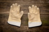 Pair work gloves lying on planks of wood — Stock Photo