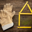 House concept with yellow meter and working gloves on wooden — Stock Photo #62091453