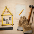 House concept with yellow meter and working gloves on wooden — Stock Photo #62091461