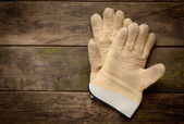 Working gloves on old wooden background — Stock Photo