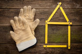 House concept with yellow meter and working gloves on wooden — Stock fotografie