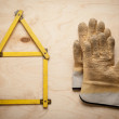 House concept with yellow meter and working gloves on wooden — Stock Photo #62133985