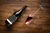 A bottle of wine and wine glass on old wood background. — Stock Photo