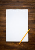 White blank papers in a copybook with pen on the wooden background — Stock Photo