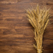 Wheat Ears on the Wooden Table. Sheaf of Wheat over Wooden. Harvest concept — ストック写真 #68249437