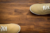 Concept with green sneakers laid on wooden floor. — Stock Photo