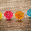 Colourful cocktail umbrellas lying on a wooden backdround, conceptual for partying and festivity — Stock Photo #77040517