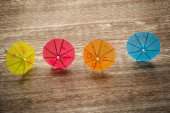 Colourful cocktail umbrellas lying on a wooden backdround, conceptual for partying and festivity — Stock Photo
