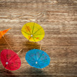 Colourful cocktail umbrellas lying on a wooden backdround, conceptual for partying and festivity — Stock Photo #78608690