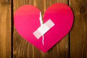 Close up of a plaster and paper broken heart on wooden backgroun — Stock Photo