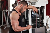 Bodybuilder looking at his phone — Stock Photo