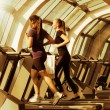 Gym shot, two young women running on machines, treadmill — Stock Photo #69774965