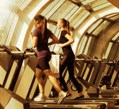 Gym shot, two young women running on machines, treadmill — Foto de Stock