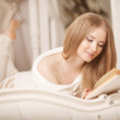 Girl reading book. Beautiful young woman lying on the sofa readi — Stock Photo #52156419