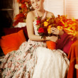 Young beautiful woman in vintage dress on autumn porch. Beauty girl in fall orange leaves — Stock Photo #52156451