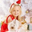 Beautiful little Santa girl near the Christmas tree. Happy girl — Stock Photo #52157989