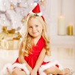 Beautiful little Santa girl near the Christmas tree. Happy girl — Stock Photo #52158005