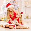 Mother and daughter dressed as Santa celebrate Christmas. Family — Stock Photo #52158125