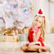 Beautiful little Santa girl near the Christmas tree. Happy girl — Stock Photo #52158135