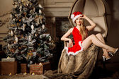 Young beauty smiling santa woman near the Christmas tree. Fashio — Foto de Stock