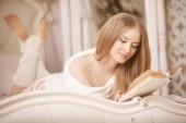 Libro de lectura de la chica. hermosa joven tumbado en el sofá readi — Foto de Stock