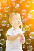 Child blowing a soap bubbles. Boy playing. Kid blowing bubbles o — Stock Photo
