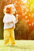 Child blowing a soap bubbles. Kid blowing bubbles on nature. Bab — Stock Photo
