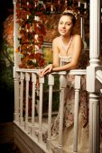 Young beautiful woman in vintage dress on autumn porch. Beauty g — Stock Photo