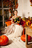 Young beautiful woman in vintage dress on autumn porch. Beauty g — Stok fotoğraf