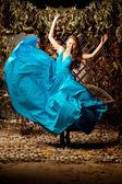 Beautiful woman in a long blue dress. Young girl in luxury fashi — Stok fotoğraf