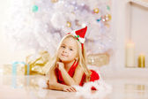 Beauty little Santa girl near the Christmas tree.  Happy girl wi — Stock Photo