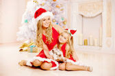 Mother and daughter dressed as Santa celebrate Christmas. Family — Stockfoto