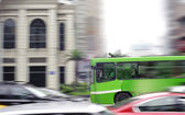 Busy city street and indistinct bus — Stock Photo