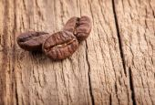 Coffee grains on old wooden board — Stock Photo