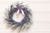 Wreath with lavender flowers on lace fabric background — Stock Photo
