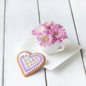 Cup full of pink  mum flowers and  heart shape cookie on white w — 图库照片