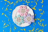 Flowers shaped cookies decorated with ornaments on blue backgrou — Stock Photo