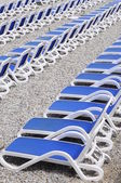 Blue sunbeds on pebble beach — Stock Photo