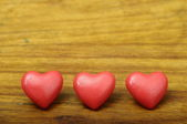 Three red heart on wooden background — Stock Photo