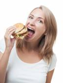 Funny girl eating burger isolated on white background — Stock Photo