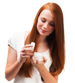 Young red-haired girl holding a package with a face cream. Isola — Stock Photo