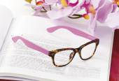 Reading glasses endorsed on a book at home — Stock Photo