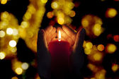 Two hands illuminated by  a candle in the darkness — Stock Photo