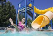 Girl splashing on the slide — Stock Photo