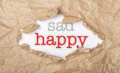 Happy and sad words on paper and torn cardbox — Stock Photo