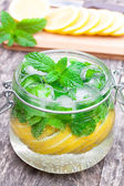 Homemade fruit drink with lemon mint and ice on the table — Stock Photo